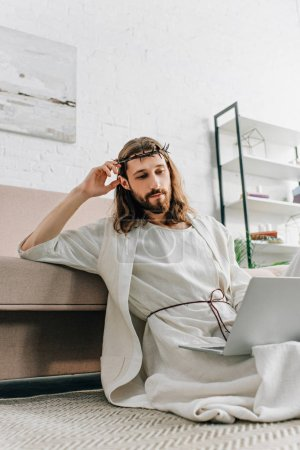 confident Jesus in crown of thorns sitting on floor and using laptop near sofa at home