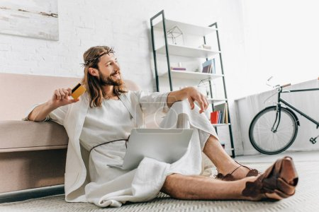 smiling Jesus sitting on floor with credit card and doing online shopping on laptop near sofa at home