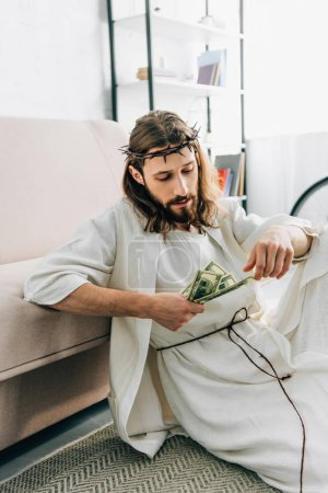 selective focus of Jesus sitting on floor near sofa and counting cash at home