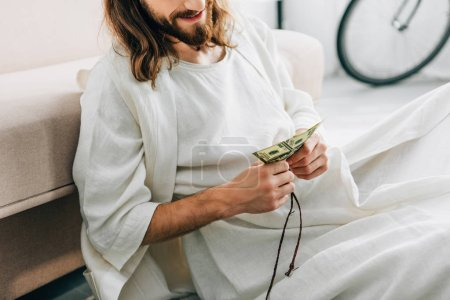 partial view of Jesus sitting on floor near sofa and counting cash at home
