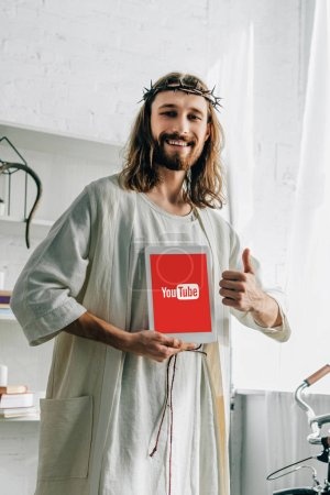 cheerful Jesus in crown of thorns doing thumb gesture and showing digital tablet with youtube at home