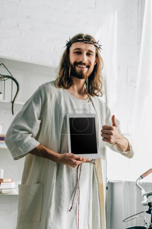 happy Jesus in crown of thorns doing thumb gesture and showing digital tablet with blank screen at home