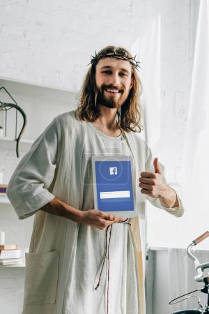 smiling Jesus in crown of thorns doing thumb gesture and showing digital tablet with facebook website at home