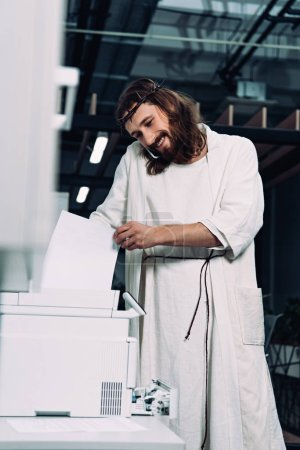 cheerful Jesus in crown of thorns and robe talking on smartphone and using copy machine in modern office