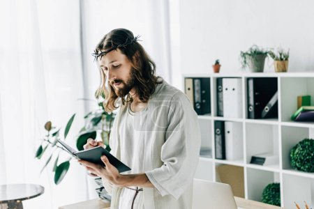 serious Jesus in crown of thorns and robe writing in textbook near working table in modern office