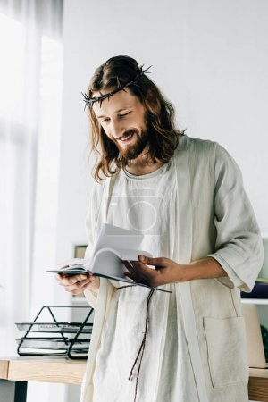 selective focus of happy Jesus in crown of thorns and robe reading textbook near working table in modern office