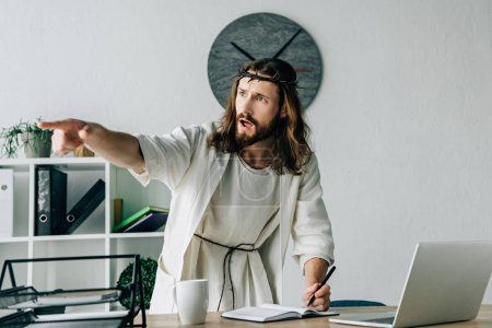 aggressive Jesus in crown of thorns and robe writing in textbook and pointing by finger at table with laptop in modern office