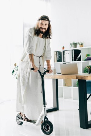 happy Jesus in crown of thorns and robe riding on kick scooter in modern office