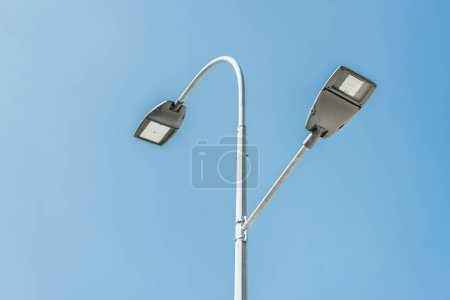 low angle view of street lamps against blue sky