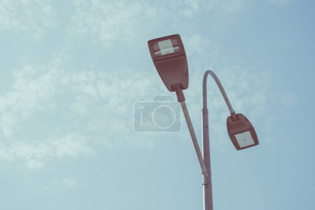 low angle view of street lamps against blue sky, toned image