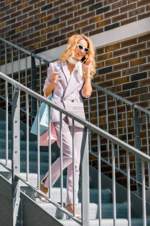 attractive fashionable woman with paper bags talking by phone on stairs