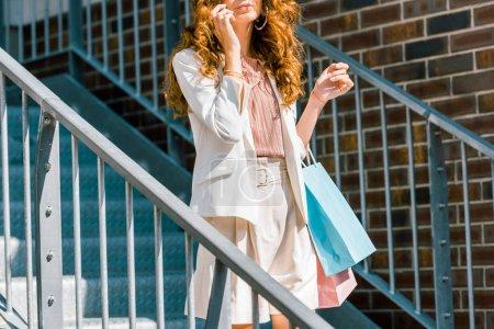 Photo pour Recadrée coup de jeune femme avec des sacs de papier parler par téléphone dans les escaliers - image libre de droit