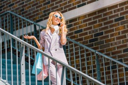 Photo pour Vue de dessous de femme heureuse élégante avec des sacs de papier parler par téléphone dans les escaliers - image libre de droit