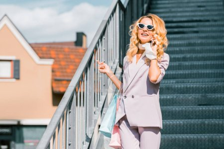 stylish young woman with paper bags talking by phone on stairs