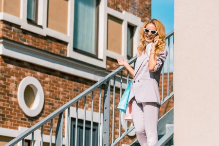 fashionable young woman with paper bags talking by phone on stairs