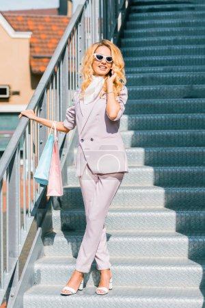 Photo pour Belle jeune femme avec des sacs de papier parler par téléphone dans les escaliers - image libre de droit
