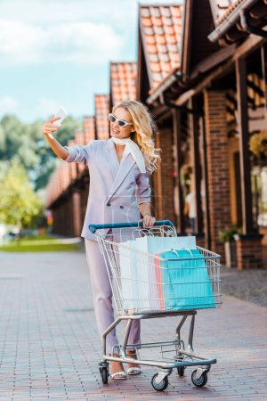 beautiful young woman with shopping cart full of paper bags taking selfie on street