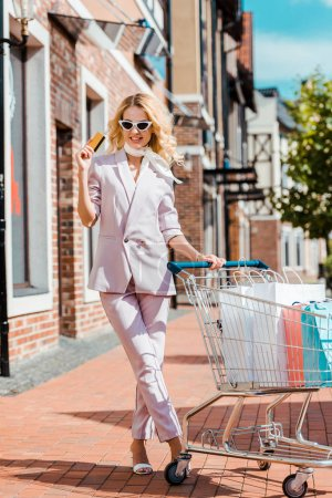 fashionable young woman with shopping cart full of paper bags holding credit card