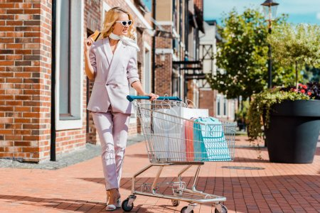 beautiful young woman with shopping cart full of paper bags holding credit card and looking away