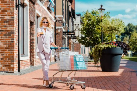 stylish smiling woman with shopping cart full of paper bags holding credit card