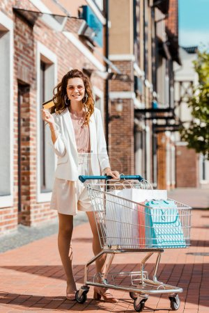 fashionable smiling woman with shopping cart full of paper bags holding credit card