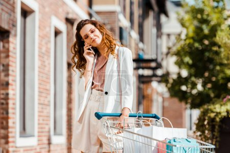 attractive young woman with shopping cart full of paper bags talking by phone