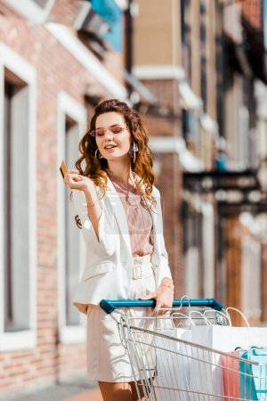 happy young woman with shopping cart full of paper bags holding credit card