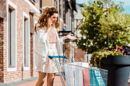 Photo for Angry young woman with shopping cart full of paper bags talking by phone - Royalty Free Image