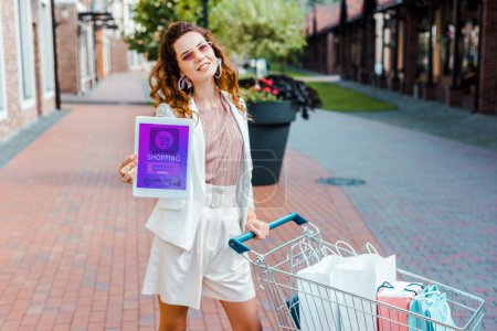 beautiful young woman with shopping cart full of paper bags showing tablet with shopping app on screen at camera