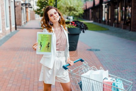 beautiful young woman with shopping cart full of paper bags showing tablet with best shopping app on screen at camera