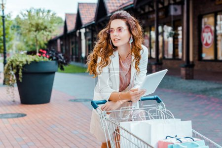 beautiful stylish woman with shopping cart full of paper bags using tablet