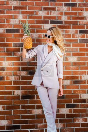stylish young woman with pineapple standing in front of brick wall
