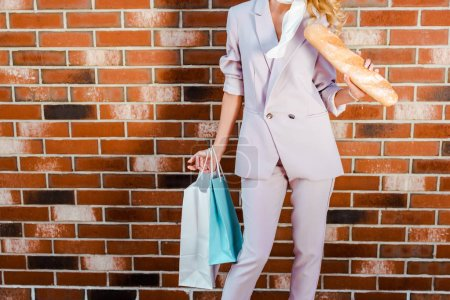 cropped shot of woman with baguette and shopping bags standing in front of brick wall
