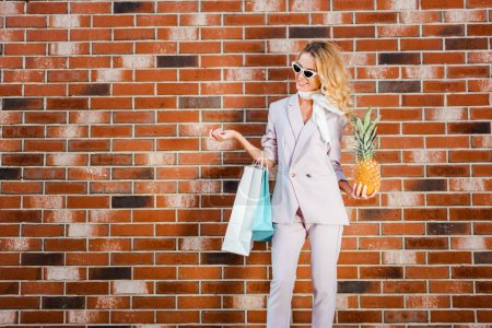 beautiful young woman with pineapple and shopping bags standing in front of brick wall
