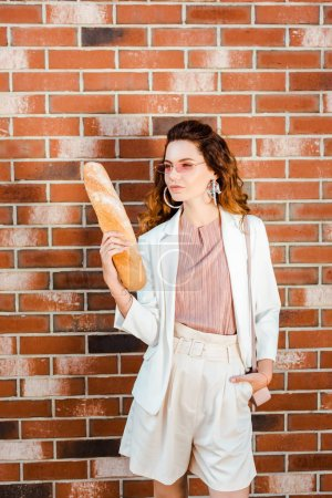 Photo for Stylish woman in shorts with baguette standing in front of brick wall - Royalty Free Image