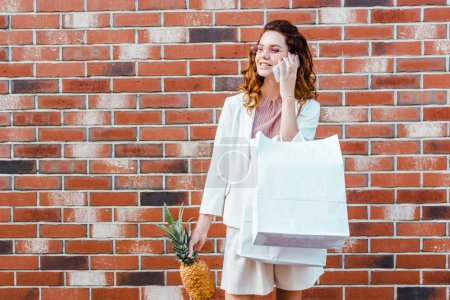 beautiful young woman with pineapple and shopping bags talking by phone in front of brick wall