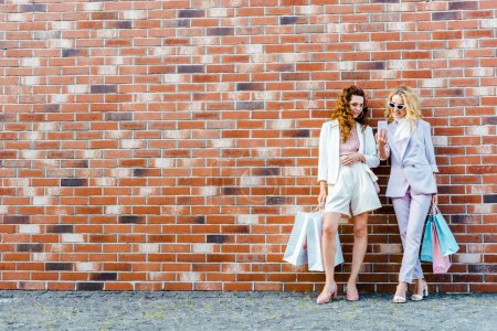 Photo for Beautiful young women with shopping bags using smartphone while standing in front of brick wall - Royalty Free Image