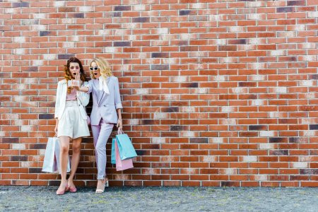 shocked young women with shopping bags taking selfie while standing in front of brick wall
