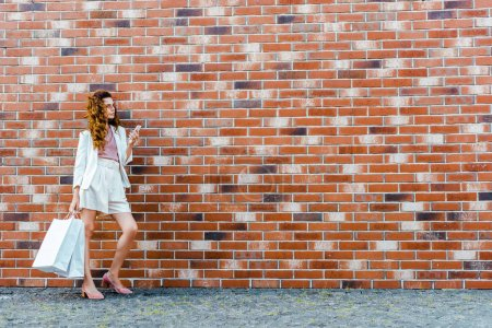 stylish young woman with shopping bags using smartphone in front of brick wall