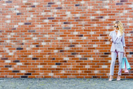 stylish young woman with shopping bags using smartphone while standing in front of brick wall