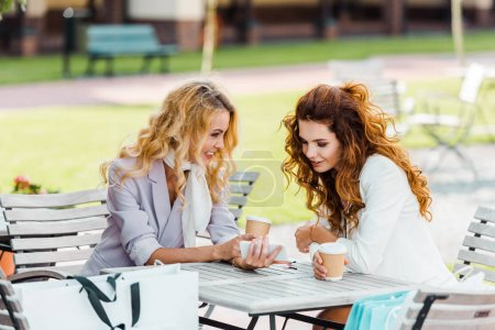 Photo for Attractive young women using smartphone while spending time together in cafe after shopping - Royalty Free Image