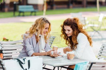 Photo pour Séduisantes jeunes femmes à l'aide de smartphone tout en passer du temps ensemble au café après le shopping - image libre de droit