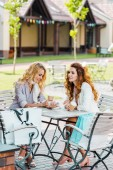 fashionable young women using smartphone while spending time together in cafe after shopping