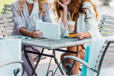 recadrée tir des jeunes femmes avec carte de crédit et de la tablette faisant e-shopping assis dans le café