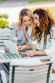 attractive young women with credit card and tablet making e-shopping sitting in cafe