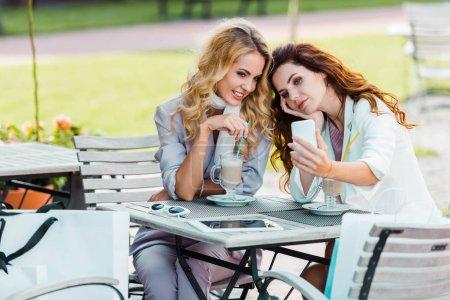 Photo pour Belles jeunes femmes prenant selfie assis au café après le shopping - image libre de droit