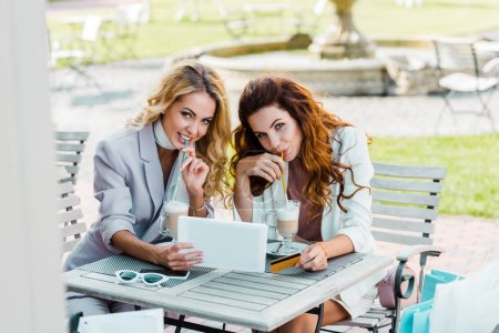 beautiful young women using tablet together while sitting in cafe after shopping