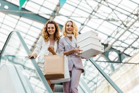 fashionable young women with shopping bags and boxes on escalator at mall