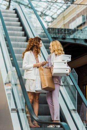 stylish young women with shopping bags and boxes on escalator at mall