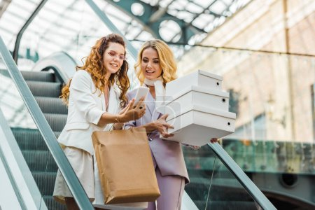 Photo for Beautiful young women with shopping bags and boxes looking at smartphone on escalator at mall - Royalty Free Image